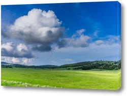Постер Пейзаж с холмистым рельефом и зеленой травой.