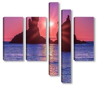 Модульная картина Солнце всходит между двумя скалами братьями близнецами, которые возвышаются над морской рябью